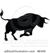 Vector Illustration of a Black Silhouetted Bull Charging by AtStockIllustration