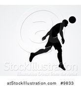 Vector Illustration of a Black Silhouetted Male Soccer Player Head Passing a Ball, over Gray by AtStockIllustration