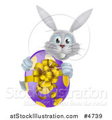 Vector Illustration of a Gray Bunny Holding an Easter Egg by AtStockIllustration