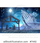 Vector Illustration of Engraved Praying Hands over a Silhouetted Christmas Nativity Scene at the Manger with the Star of Bethlehem and City in Blue Tones by AtStockIllustration